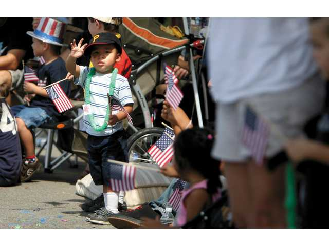 Noah Purnell, 2, of Valencia, waves as the parade makes its way down Lyons.