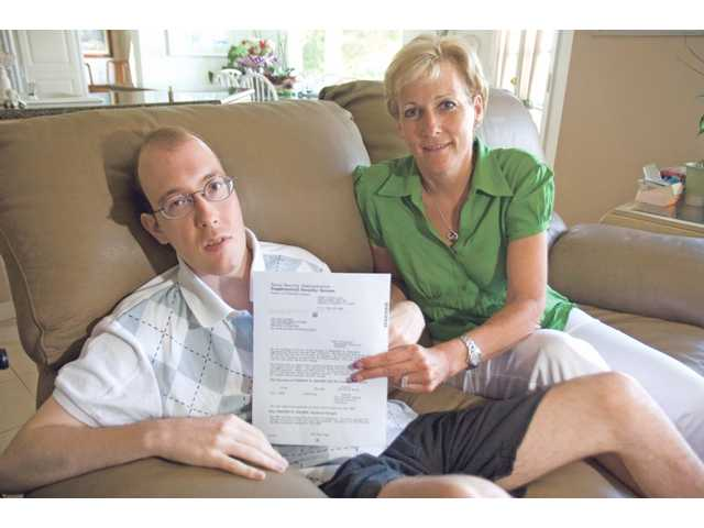 Tim Holmes, 23, and his mother LeeAnn Holmes hold a letter they received from Social Security, stating an 8-percent decrease in his disability check. Tim has had more than 130 brain surgeries for his uncontrolled hydrocephalus, which is head swelling from fluid in his brain cavity.