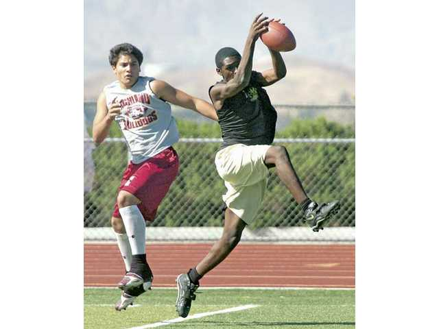 Grizzlies defensive back Corey Chaisson, right, tries to pick off a pass Thursday at Golden Valley.