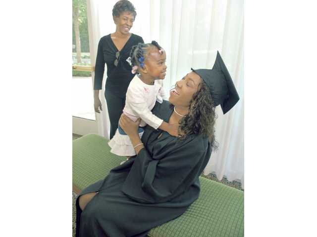 Grandmother Bertha Clark, left, looks on as 2-year-old Syrai Piper gives her mother Catresa Clark a hug while she prepares for her graduation ceremony Friday.