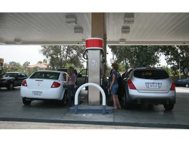 Valencia residents Chelsea Lowrey and Sue Grubbs pump gas at the Shell stationat the corner of McBean Parkway and Valencia Boulevard Wednesday afternoon.