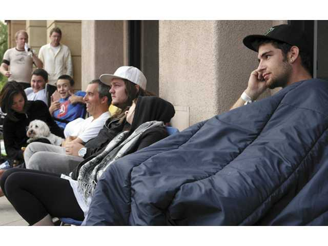 Jeremy Whitcomb, a 19-year old College of the Canyons student, waits patiently at the front of the line at the AT&T Wireless store in Santa Clarita on Friday, just minutes before the highly anticipated Apple iPhone 3G went on sale at 8 a.m.