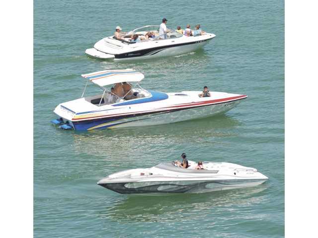 Pleasure boats cross paths near the Castaic Lake main boat launch on Saturday.