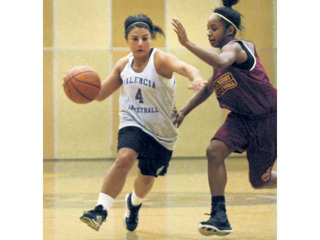 Valencia's Madison Lanc (4) fights at midcourt against Alemany Saturday at the College of the Canyons.