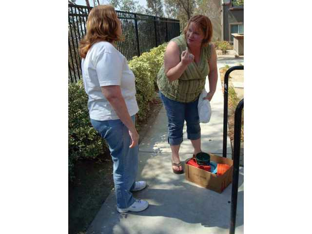 Cindy James, left, of Castaic, picks up kitchenware that Trina Stopen, of Canyon Country, gave her through Santa Clarita Freecycle.