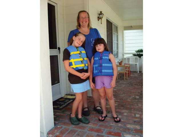 Kathy Singly, center, received a set of free life jackets for her daughters Terri, 7, left, and Andi, 6, right, through Santa Clarita Freecycle.
