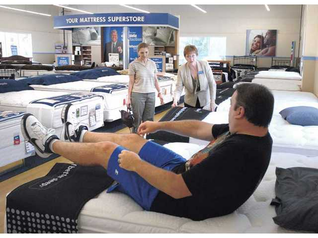 Sale Representative Claudette Parker, center, assists customers Dax, on bed, and Lili Wagner as they sample mattresses that have been suggested for them by the Sleep To Live scientific diagnostic system at Sit n' Sleep on Friday.