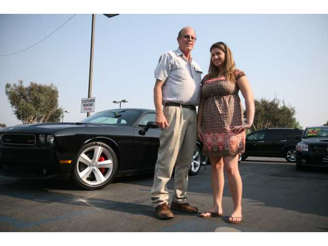 Jim Nyholt, from Palmdale and friend Stacey Meyer, from Quartz Hill, stand in front of Nyholt's new Dodge Challenger. Nyholt, who owned a 1971 model, picked up the new car Thursday evening.
