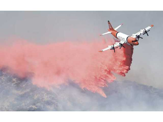 An Aero Union P-3 tanker makes a drop near the Osito Canyon area near Pyramid Lake after a wildfire broke out Monday afternoon. The fire backed up traffic north of Templin Highway after lanes three and four of Interstate 5 were closed by the CHP.
