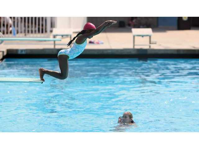 Eight-year-old Brittany Giles takes a dive off the SCV Aquatic Center diving board Thursday morning during her swim class.