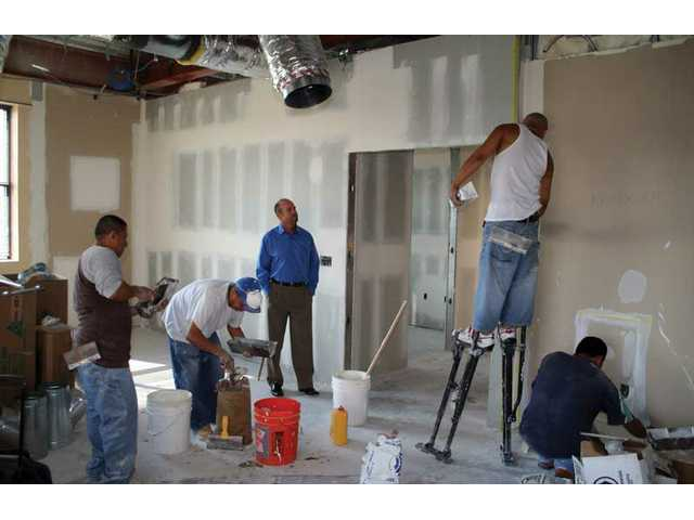Tim Borruel, center, superintendent of Legacy Christian Academy, watches as construction workers turn the bottom floor of the RE/MAX building next door to the school into classrooms.