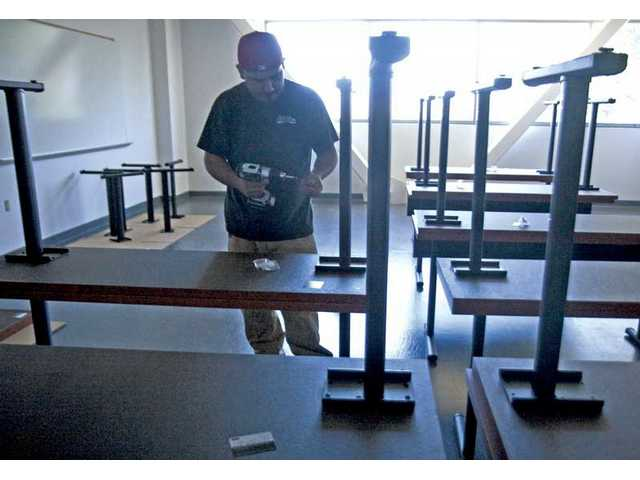Armando Mendez, of BKM Office Environment, assembles desks inside the Dr. Dianne G. Van Hook University Center on Monday. COC's fall session classes is scheduled to begin August 24.