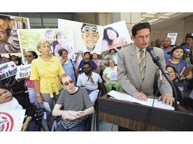Newhall resident LeeAnn Holmes, left, and her son, Tim, look on as Rabbi Jonathan Klein, executive director of Church and Laity United for Economic Justice, speaks at a rally in downtown Los Angeles in protest of the state's budget cuts to disabled citizens.