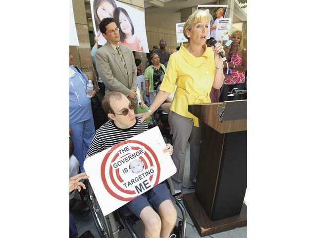 Newhall resident LeeAnn Holmes, right, speaks on behalf of her disabled son, Tim, at a rally in downtown L.A. in protest of the state's social services budget cuts.