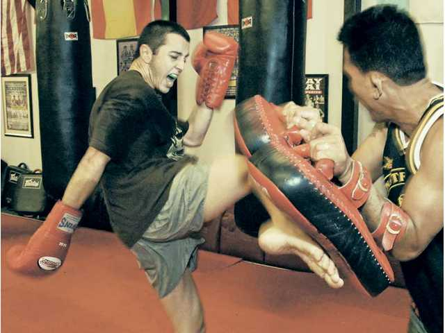 Eighteen-year old Ruben Lahn, left, spars with Kru Pongsan Ekyotin at World Muay Thai Tuesday in Canyon Country. Lahn, a Canyon Country resident, is training for the 2009 Ultimate Warriors Muay Thai Kickboxing World Championship Saturday in Anaheim.