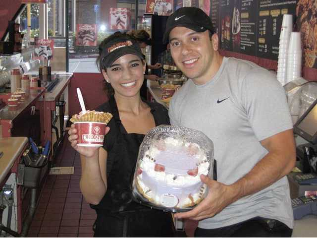 Katie Rosen and owner Eddie Buraye show two of the delicious things you can find at the Cold Stone Creamery on McBean Parkway in Valencia - strawberry ice cream and more in a waffle cone, and a Strawberry Cheesecake Paradise ice cream cake.
