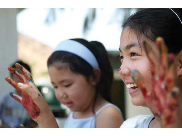 Noelle Min, 10, shows off her colorful hands after a session of painting, during the first day, of the first session of the Summer Adventure Camp at Tesoro Adobe Historic Park on Monday afternoon.