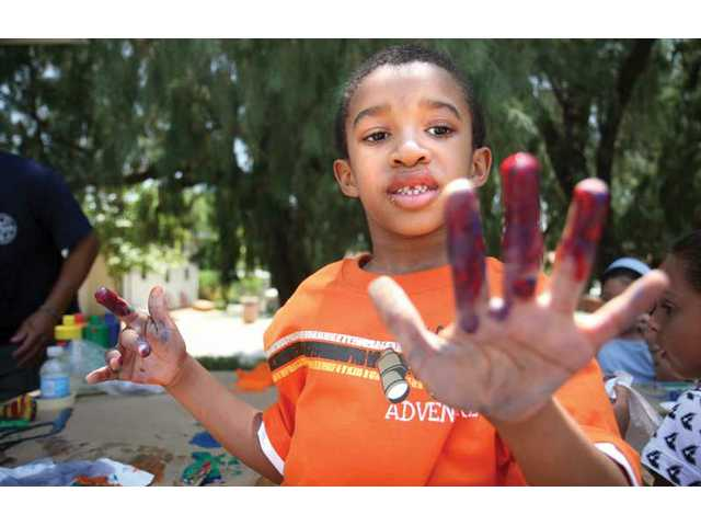 Brandon Crockett, 6, checks out his hands covered in paint, after finishing his art project, during day one of the Summer Adventure Camp.