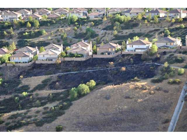 A brush fire threatened homes in Castaic Thursday before firefighters extinguished the flames.