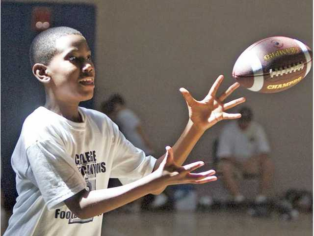 Nicholas Hogan, 11, makes a catch Thursday during the fifth annual COC Youth Football Camp.