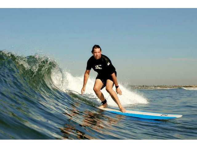 Eric Christiansen rides a gentle wave at Surfside Beach, just south of Huntington Beach.