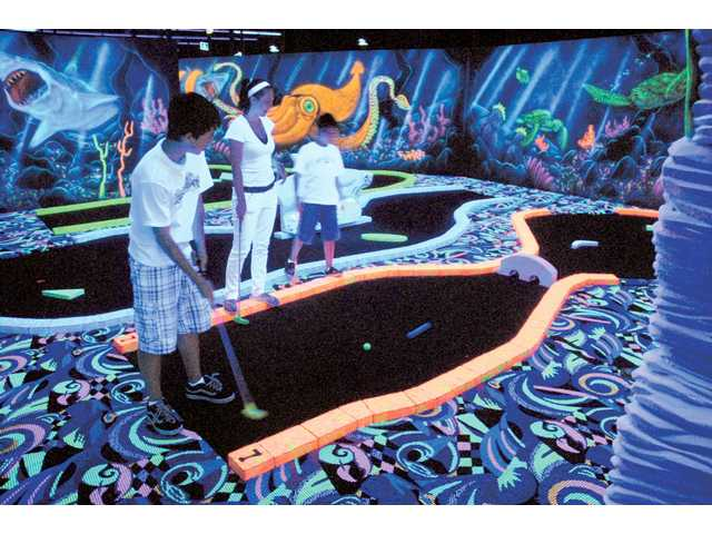 Brandon Yukawa, 16, left, attempts a putt as he plays a round of blacklight miniature golf with his sister, Brittany, 18, and brother Jeremy, 10, at Fin's Glow Zone, an underwater-themed miniature golf course illuminated by blacklights.