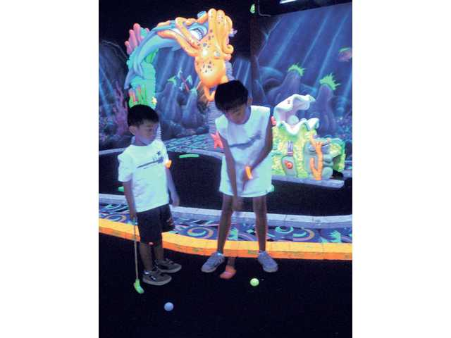 Jordan, 4, and Jake Boonyanetr, 8, play a round of golf at Fin's Glow Zone's underwater-themed blacklight miniature golf course on Wednesday.