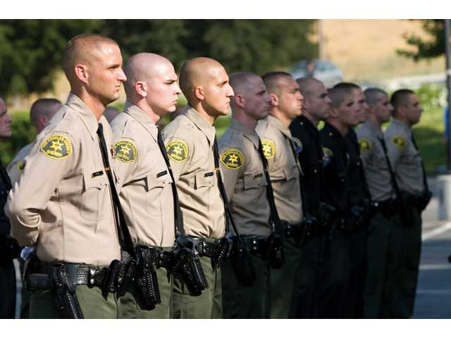 Members of Sheriff's Academy Class No. 372 stand at parade rest during Thursday's graduation ceremony at the College of the Canyons. Forty-three deputies and officers graduated from the program.