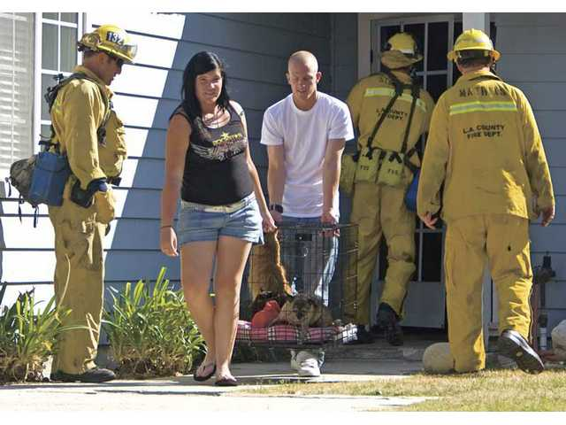 Leann and Christopher Crone help carry their two cats and a dog out of their home on Mustang Road Friday afternoon after a voluntary evacuation was issued for the Castaic neighborhood due to the Sloan fire.