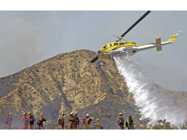 A water-dropping helicopter makes a delivery near a camp crew during the Sloan Fire on Friday afternoon.