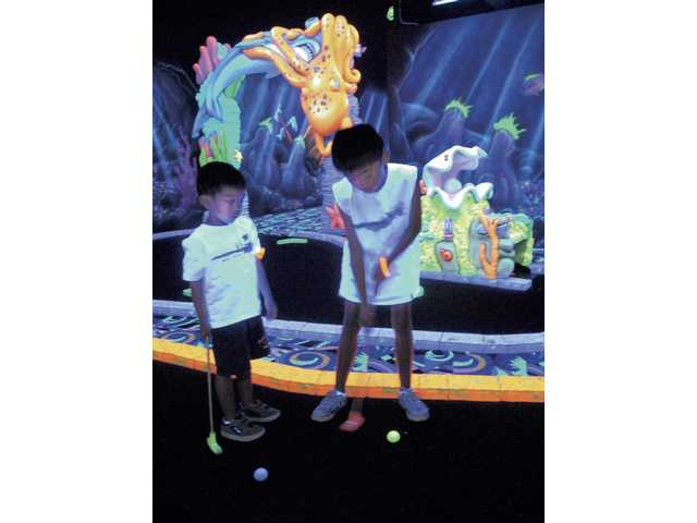 Jordan Boonyanetr, 4, and his brother Jake, 8, play a round of miniature golf at Fin's Glow Zone, an underwater-themed blacklight miniature golf course in Valencia on Wednesday.