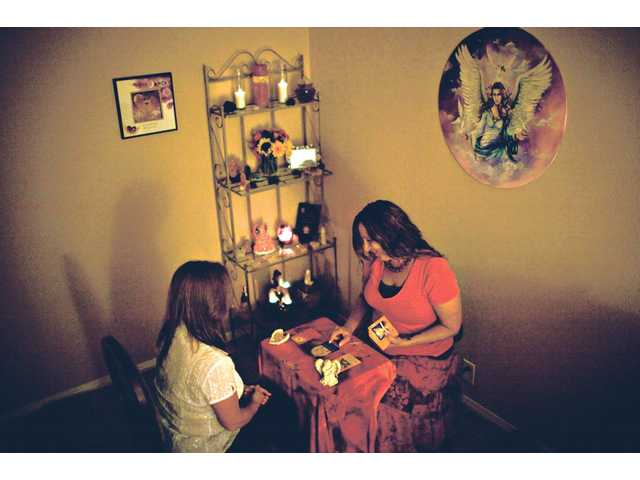 Darlene, right, gives an angel card reading to a client.  Darlene has been practicing angel card therapy since 2006.