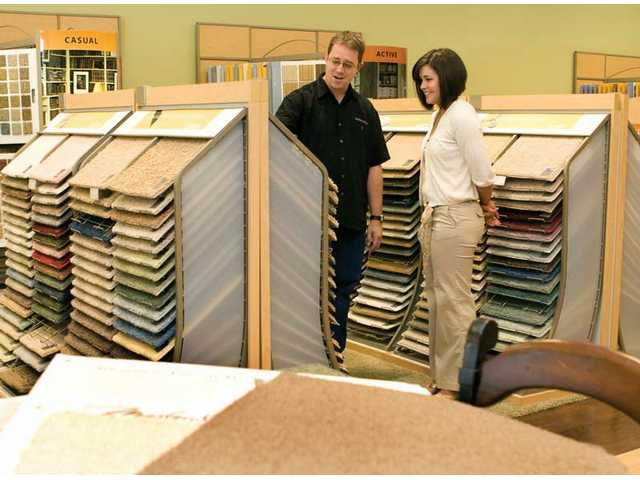 Ben Griffiths, part owner of Brent's Carpets in Newhall with his father Brent, shows Maria Castillo a selection of carpet samples on Wednesday. Brent's Carpets will be coming up on 30 years of business next year.
