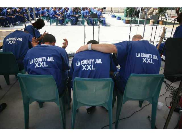 Members of the musical group Contra Band prays together during the MERIT graduation ceremony, at Pitchess Detention Center on Friday. Nearly 100 Los Angeles County Jail inmates graduated from the program.