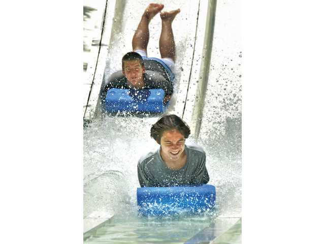 Darren Hewitt, 14, left, and Ian Scory, 15, keep cool on the Bamboo Racer water slide at Six Flags Hurricane Harbor on Friday.