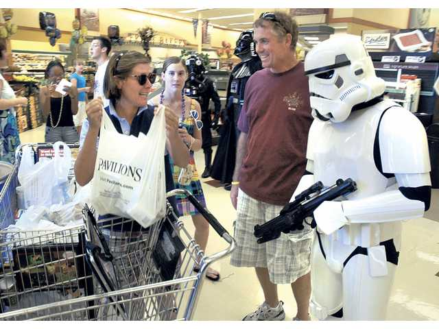 Marilyn Boss, left, and her husband Steve donate two bags of food at the canned food drive held at Pavilions on McBean Parkway on Saturday. All donated items went to the Santa Clarita Food Pantry. The 501st Legion, a worldwide Star Wars costuming organization, offered photo opportunities to fans in exchange for food donations.