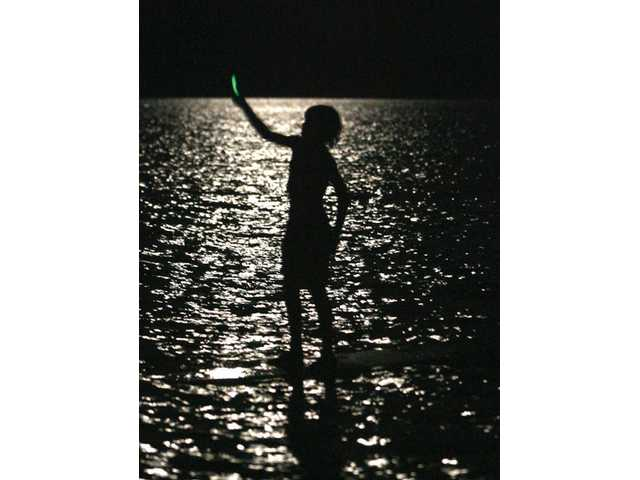 A junior lifeguard waves the participants in the 13th annual Night Crawler race toward the shore at Castaic Lake on Thursday night. More than 70 lifeguards took part in the race.