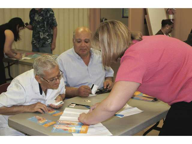 Corie Hill, right, a transit division administrative analyst, guides two seniors through the Transit Access Pass process at the Santa Clarita Valley Senior Center on July 8 in Newhall. The city of Santa Clarita transit facility provided information booklets for seniors at a Transit Access Pass workshop.