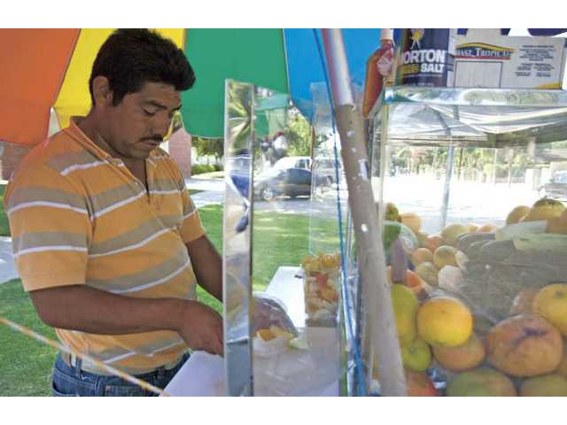 Jose Flores cuts a variety of fruits Monday afternoon in Newhall. Temperatures reached triple digits Monday.