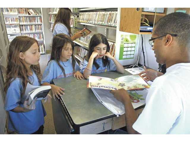 Katie Bluma, 7, left, Madison Maginn, 8, and Brianna Dzyuba discuss the reading incentive program with library assistant Tiarrie Gaddis, right, at the SCV Bookmobile.
