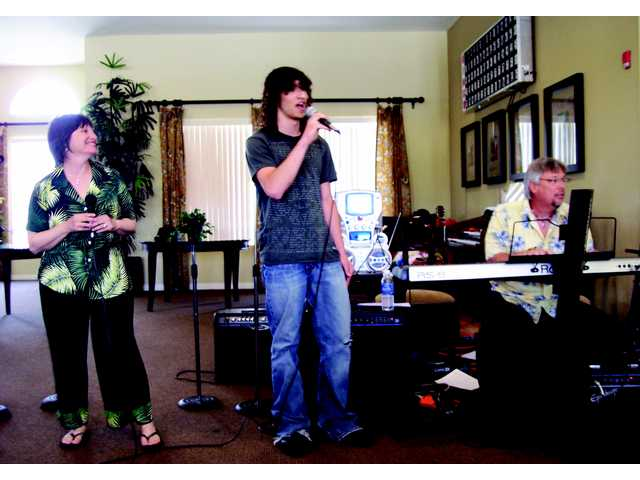 Katherine Lench-Meyering, left, Max Meyering, center, and Dennis Poore, right, entertain the seniors at the Fountain Glen senior complex in Valencia during a benefit performance.