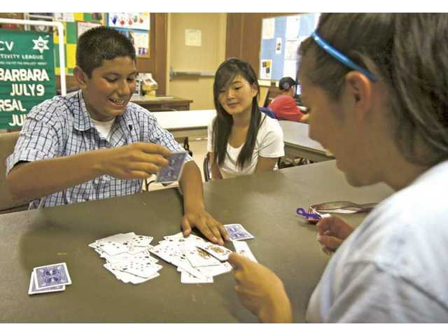 "Michelle Kim, center, watches David Bobadilla and Vanessa Lopez play a card game called ""Speed"" at Val Verde Park on Monday."
