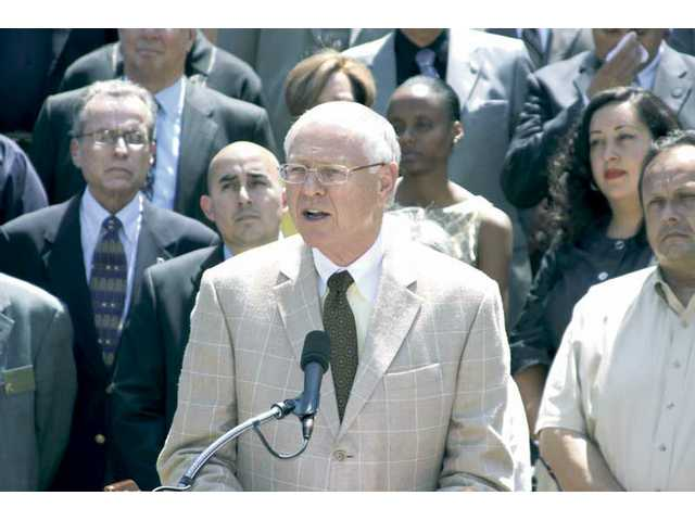 Mike Antonovich, center, and more than 50 politicians from across Los Angeles County protested the spending plan outside the Hall of Administration near dowtown Los Angeles on Wednesday.