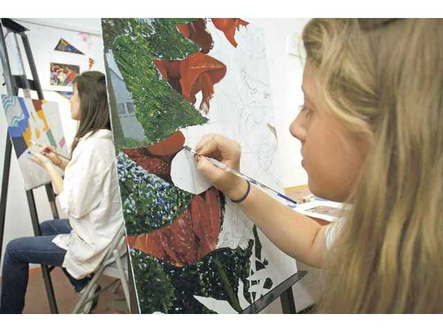 "West Ranch High School student Kassandra Lewis, 17, right, works on her oil painting with the theme ""forest and comedy"" in a painting class at the California Institute of the Arts InnerSpark program on Wednesday."
