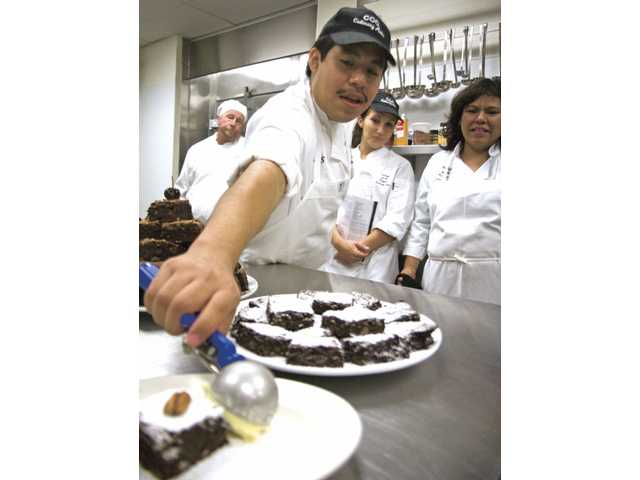 Carlos Ramirez, of Newhall, tops a baking dish with a scoop of vanilla bean ice cream during the summer culinary class at the College of the Canyons Culinary Institute on Town Center Drive on Wednesday afternoon.