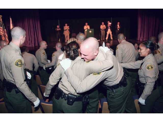Deputies celebrate after being sworn in as peace officers for the Los Angeles County Sheriff's Department during a Thursday morning graduation ceremony at the Santa Clarita Performing Arts Center.