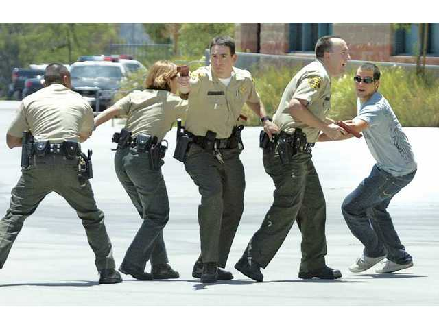 """Sheriff's Deputy Bryan Kaser, right, questions a fleeing witness, Manino Giammarco, 19, as a """"contact team"""" searches for multiple shooters in a training scenario at Valencia High School on Thursday."""