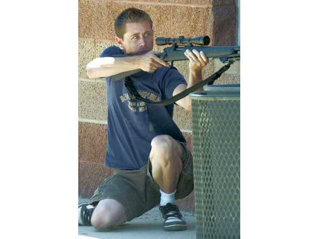 Deputy Brandon Painter takes aim as a mock shooter during the campus training scenario.