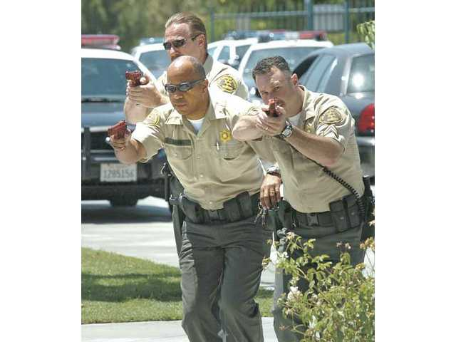 Sheriff's deputies, from left, Lance Westfall, Keith Davis and James Maxey approach a classroom in a training scenario at Valencia High School on Thursday.