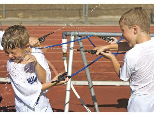 Six-year-olds Dominic Yarnall, left, and Carson Tujague spray each other with water during a break at the 2009 College of the Canyons Youth Football Camp on Thursday.